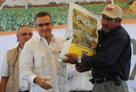 At the inaguaration of the seed program in 2011, a member of the cooperative from the Lower Lempa presents President Mauricio Funes with certified seed, as the Minister of Agriculture looks on